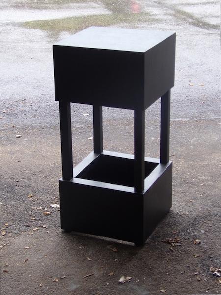 Ce tabouret, décor de spectacle, est un  assemblage de deux volumes noirs .