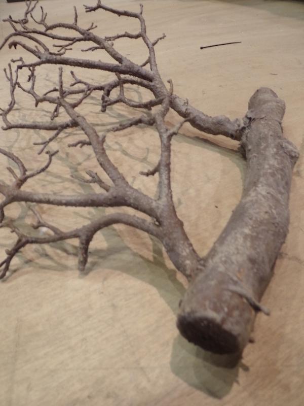 Cette branche de bois est un assemblage de morceaux factices et colorée d'une patine.