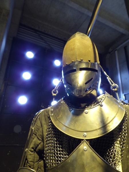Cette armure au trois quart en métal est un accessoire d'opéra éclairée d'une lumière chaude.